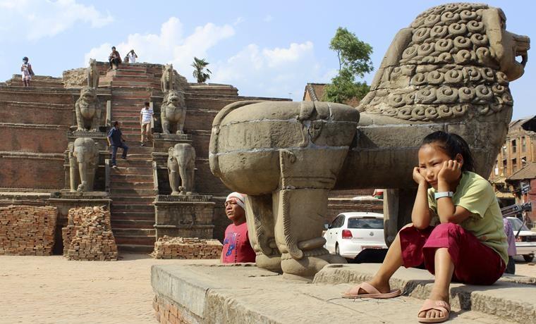 Una niña contempla los restos de monumentos derrumbados en la plaza Durbar de Bhaktapur (Nepal), declarados Patrimonio de la Humanidad por la UNESCO, que quedaron gravemente dañados por el terremoto que asoló el país asiático. Poco ha cambiado casi un mes después para muchos de los damnificados por el terremoto que asoló Nepal, que ven pasar el tiempo en localidades devastadas como Bhaktapur sin que llegue la ayuda, mientras aumenta la incertidumbre sobre su futuro. EFE/Luis Ángel Reglero