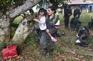 A member of the Revolutionary Armed Forces of Colombia (FARC) holds the daughter of a mate during a visit of their relatives, at a camp in the Colombian mountains on February 18, 2016. Many of these women are willing to be reunited with the children they gave birth and then left under protection of relatives or farmers, whenever the imminent peace agreement puts an end to the country's internal conflict. AFP PHOTO / LUIS ACOSTA / AFP / LUIS ACOSTA